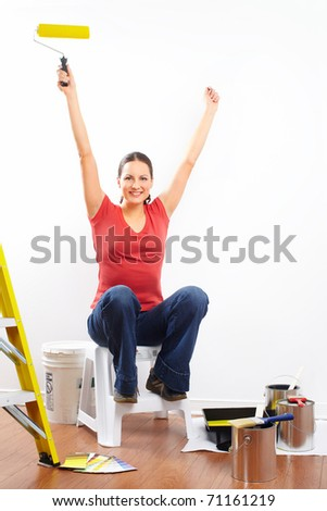 smiling beautiful woman painting interior wall of home.