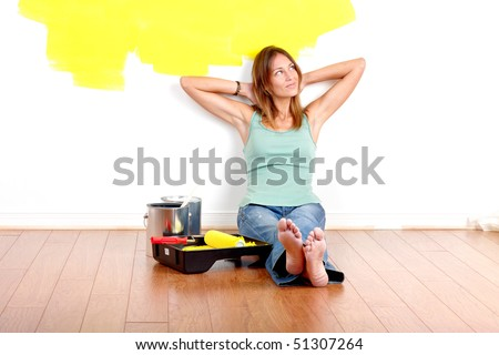 Smiling beautiful woman painting interior wall of home.  Renovation