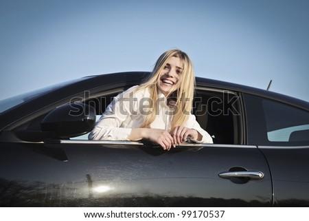Smiling beautiful woman sitting in a car