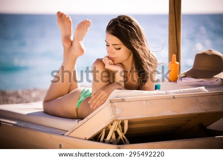 Smiling beautiful woman sunbathing in a bikini on a beach at tropical travel resort, enjoying summer holidays.Young woman lying on sun lounger near the sea.Happy serene woman having SPF protection