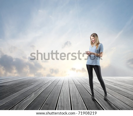 Smiling beautiful woman using a mobile phone on a wooden floor