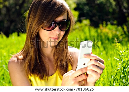 Smiling beautiful woman with mobile phone outdoor. Sunny summer day.