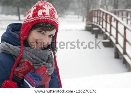Smiling beautiful woman with two red hearts in the snowy park.