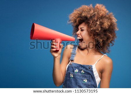 Smiling beautiful young African American woman with curly afro hair screaming by red megaphone. - Shutterstock ID 1130573195