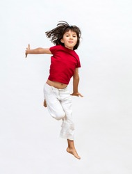 smiling beautiful young child jumping with positive energy, flying free to express cheerful success, dynamic childhood and fun open mindedness over white background, isolated