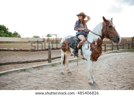 Smiling beautiful young woman cowgirl sitting and riding horse on ranch