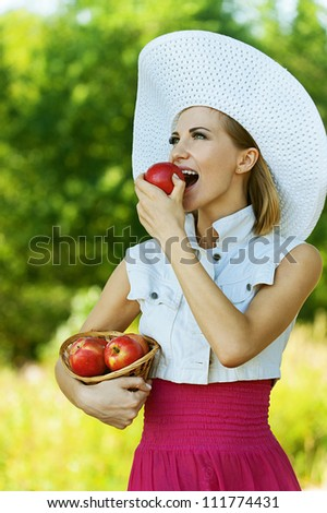 Smiling beautiful young woman in hat wiht wicker basket holds red apples, against green of summer park.