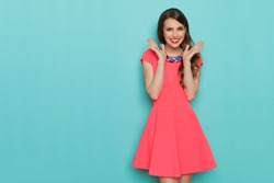 Smiling beautiful young woman in pink mini dress posing with hands on chin. Three quarter length studio shot on turquoise background.