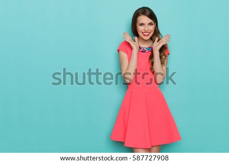 Smiling beautiful young woman in pink mini dress posing with hands on chin. Three quarter length studio shot on turquoise background. #587727908