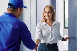 Smiling beautiful young woman opening entrance door and greeting repairman