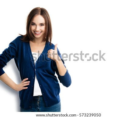 Smiling beautiful young woman, showing thumbs up gesture, isolated against white background. Caucasian brunette model in emoshions and optimistic, positive, happy feeling concept studio shoot.