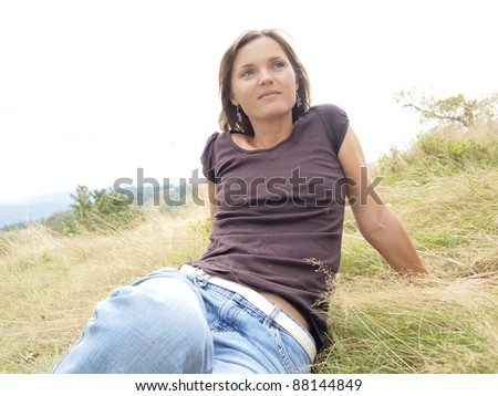 Smiling beautiful young woman sitting in the grass
