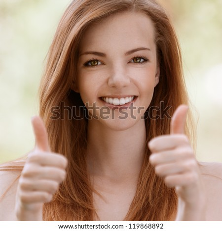 Smiling beautiful young woman with bare shoulders lifts thumbs upwards, against green of summer park.