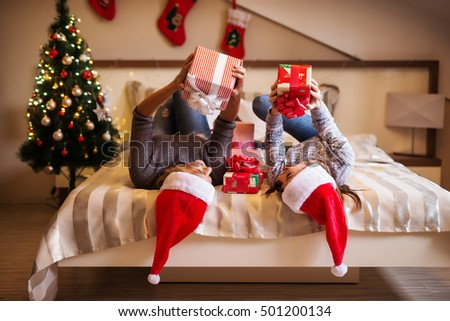 Smiling beautiful young women lying on bed with Christmas presents in their hands.
