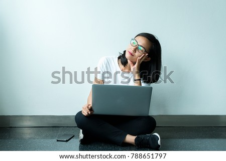 smiling beauty girl student sitting on floor with white wall background and looking at air daydreaming happy when she using laptop computer study.