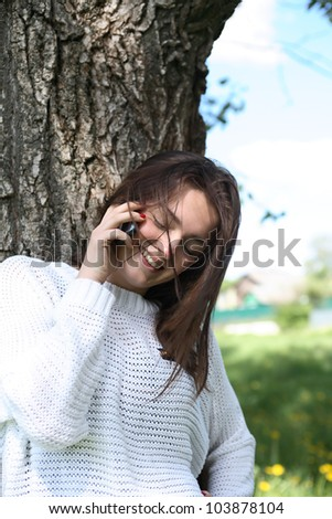 Smiling beauty teenage girl near tree talking on her mobile phone