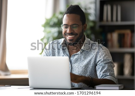 Smiling biracial man in glasses sit at desk in office browsing wireless Internet on laptop device, happy African American male worker laugh watch funny video on computer gadget, relax at work break