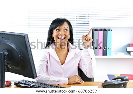 Smiling black business woman pointing up with idea at desk in office