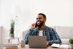 Smiling Black Businessman Talking On Phone Sitting At Workplace In Modern Office. Mobile Business Communication And Entrepreneurship. Man Having Cellphone Conversation At Work.