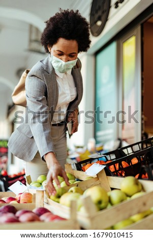 Smiling black businesswoman buying fruit while wearing protective mask on her face.