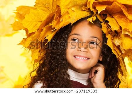 Smiling black girl wearing maple leaves crown