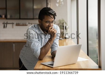 Smiling black guy freelancer stand at kitchen desk read good email message on laptop screen think on advantages proposed by customer. Young afro man hipster chat with friends online from home using pc