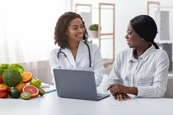 Smiling black lady doctor chatting with female patient at clinic, dietology and nutririon concept