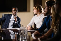 smiling black male boss talking to business team in conference room