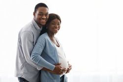 Smiling black man hugging his pregnant woman over white background