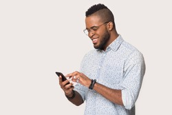 Smiling black millennial male in glasses isolated on grey background hold smartphone texting or browsing, happy african American man in spectacles using cellphone get pleasant text on mobile