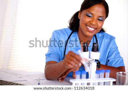 Smiling black nurse working with a test tube in blue uniform at laboratory - copyspace