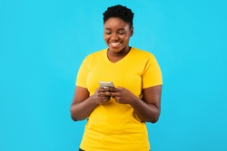 Smiling Black Oversized Lady Using Smartphone Texting Standing Over Blue Studio Background. African Millennial Woman Using Mobile Application. Happy Female Phone User Concept