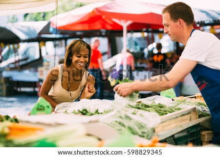 Smiling black woman buying fresh vegetables at farmer's market