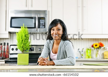 Smiling black woman in modern kitchen interior - stock photo