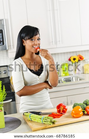Smiling black woman tasting vegetables in modern kitchen interior