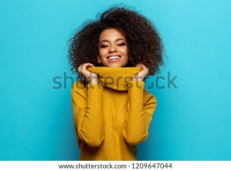 Smiling black woman wear yellow cardigan isolated on blue background