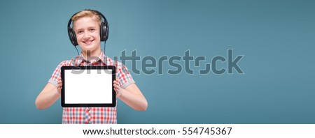 smiling blond student with headphones holding the phone at arm's length and shows the display, the lap studio shot European teenager picture with depth of field, selective focus on phone