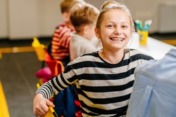 Smiling blond sweden girl sitting at desk in class room and looking at camera. Portrait of young black schoolgirl studying with classmates in background. Happy smiling pupil writing on notebook.