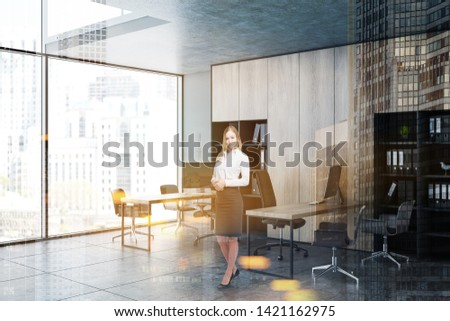 Smiling blonde businesswoman standing in panoramic office interior with gray walls and wooden bookcases and tables. Business lifestyle concept. Toned image double exposure #1421162975