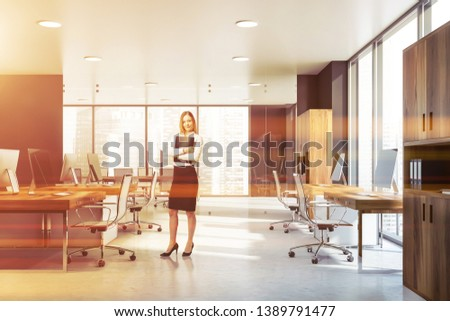 Smiling blonde businesswoman with folder standing in modern open space office with rows of wooden computer tables bookcases. Toned image #1389791477