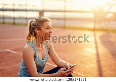 Smiling blonde Caucasian woman sitting on the court with earphones in ears and smart phone in hands in the morning.