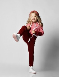 Smiling blonde curly kid girl in red sport costume and white sneakers is kicking with leg and having fun over grey wall background. Stylish casual fashion for children concept