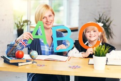 Smiling blonde English teacher plays letters and words with kid school girl, table with books in light classroom with flowerpots