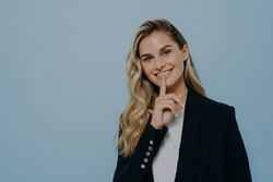 Smiling blonde girl in black coat keeping good news as secret, decides its better to wait before telling it or asking to keep silence while standing isolated on blue background. Secrecy concept