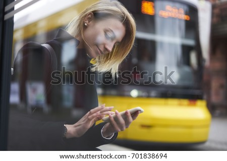 Smiling blonde hipster girl waiting for public transport on bus stop chatting in social networks via smartphone,casually dressed female tourist using application for searching traffic schedule