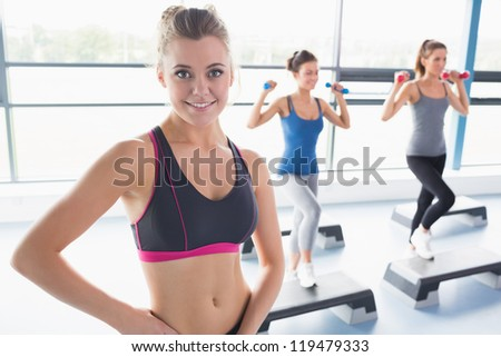Smiling blonde woman at aerobics class in gym