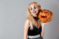 Smiling blonde woman in halloween make up posing with carved pumpkin and looking away over gray background