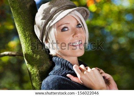 Smiling blonde woman in hat laying her back on a tree trunk