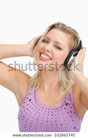Smiling blonde woman wearing headphones while touching them against a white background