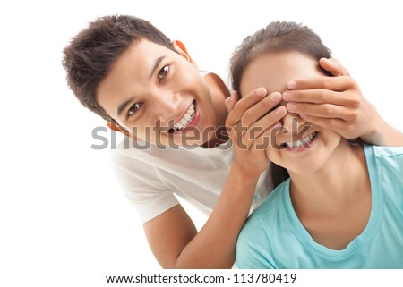 Smiling boy covering eyes of his girlfriend